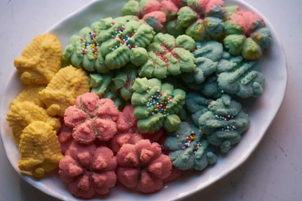 A plate of colorful Christmas cookies in various shapes, including red wreaths, gold bells, blue ornaments and green Christmas trees.