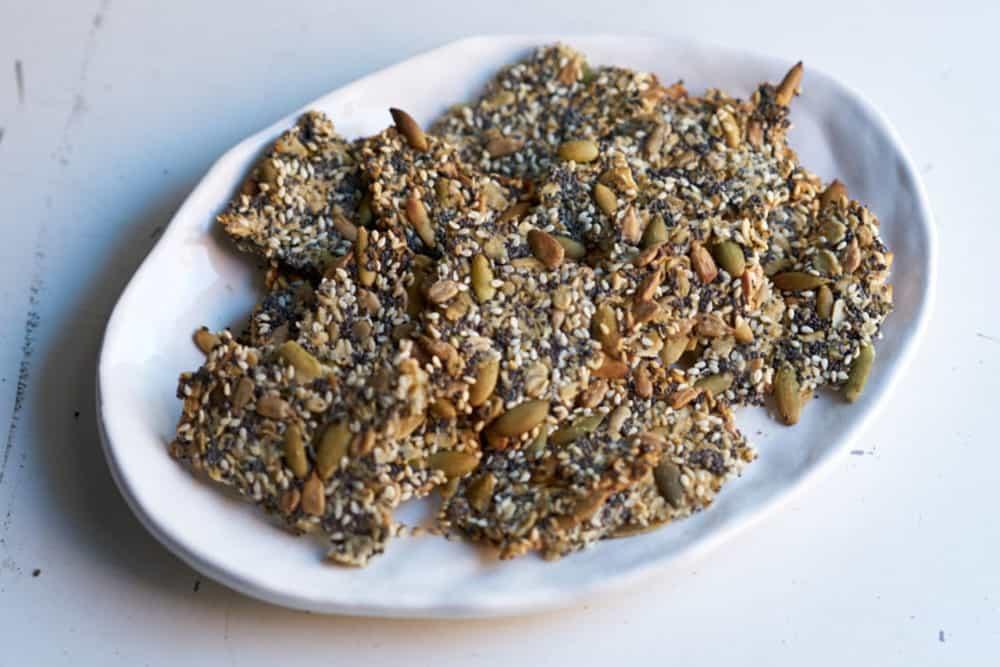 A plate of gluten free seedy oat crackers.