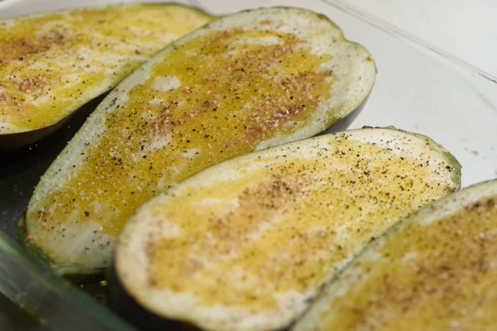 Raw eggplant halves in a baking dish, coated with olive oil, salt and pepper.
