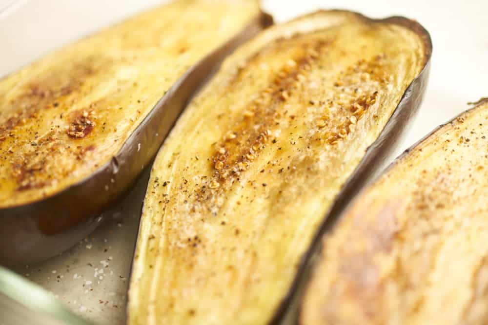Roasted eggplant halves in a baking dish.