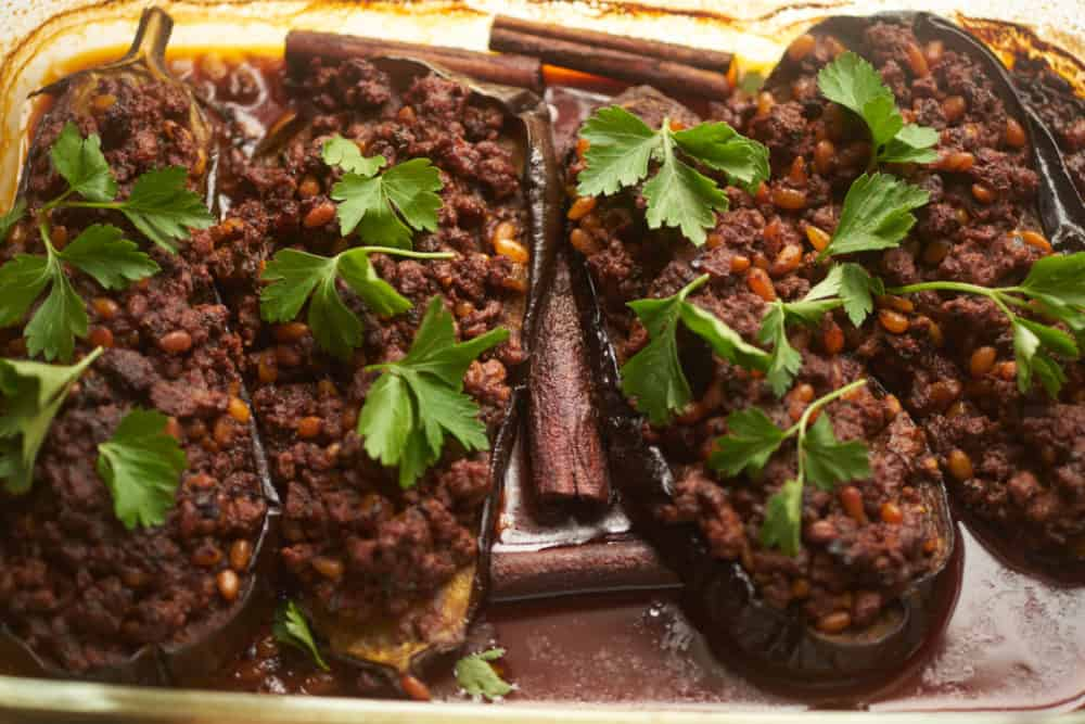 Eggplant halves stuffed with lamb and pine nuts in a glass casserole dish.