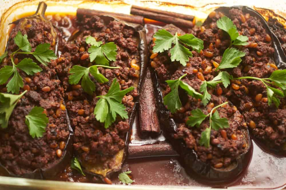 Eggplants stuffed with lamb, pine nuts and spices in a baking dish topped with parsley.