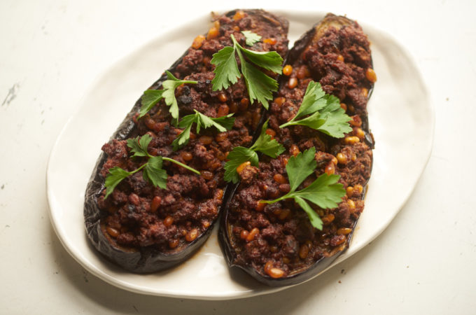 Eggplant stuffed with lamb and pine nuts, garhished with parsley on a white plate.