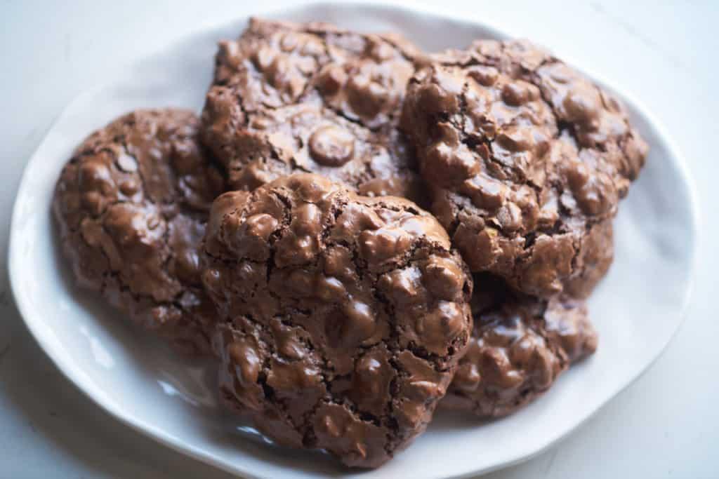 Gluten free chocolate hazelnut cookies on a white plate.