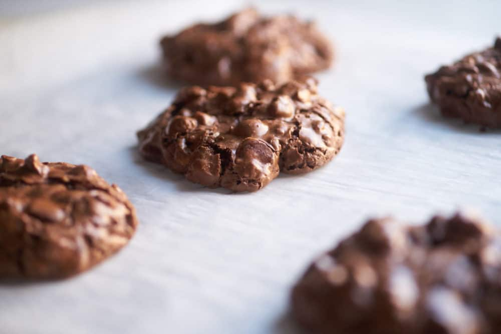 Gluten-free double chocolate hazelnut cookies cooling on a parchment sheet.