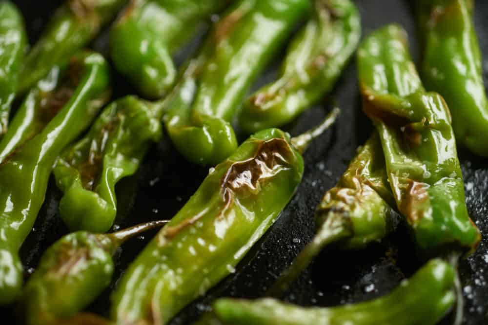 Blistered shishito peppers in a cast iron skillet.