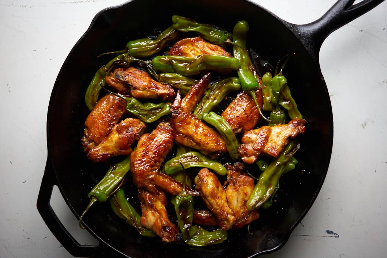 Baked chicken wings with honey, harissa, and shishito peppers in a cast iron skillet displayed on a white surface.