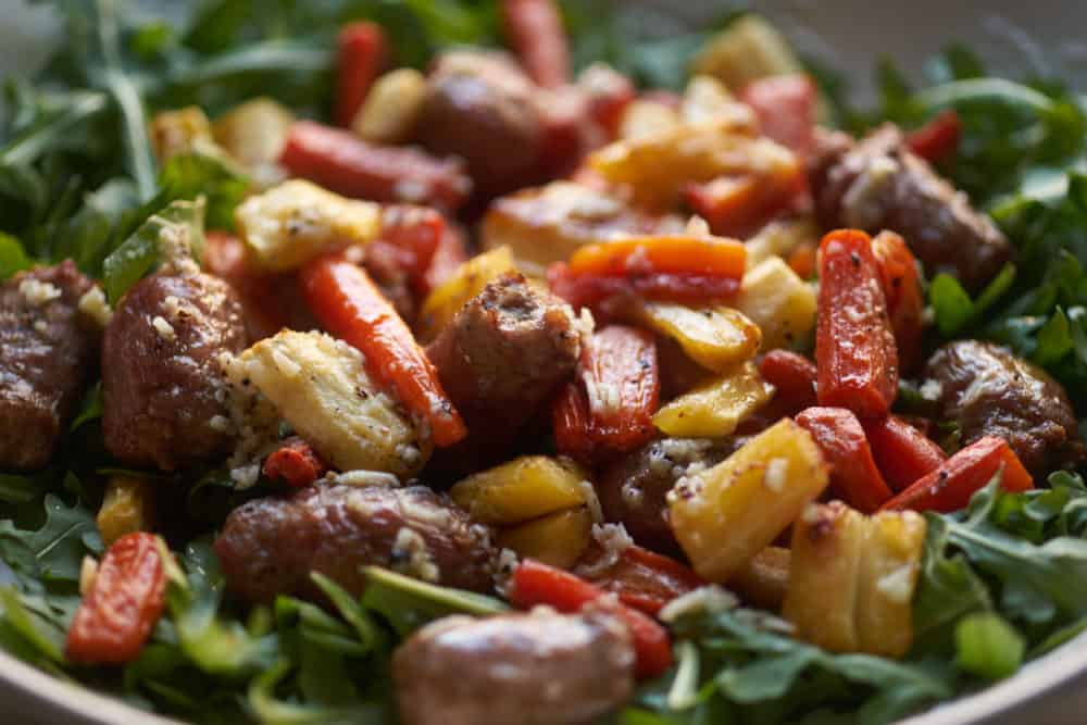 Roasted Italian sausages, carrots and parsnips tossed with parmigiano cheese, surrounded by arugula in a white salad bowl.