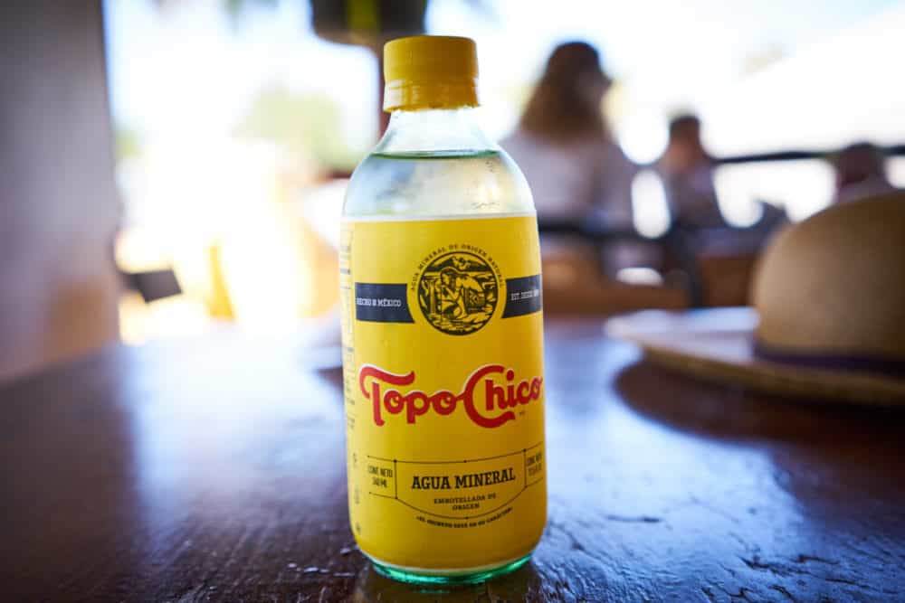 A bottle of Topo Chico water on a wooden table.