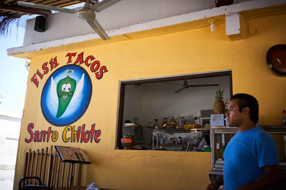 Fish Tacos Santo Chilote restaurant in Todos Santos Mexico. A yellow wall with a green chile logo to the left of a food pickup window. A waiter in a blue shirt stands to the right of the window.