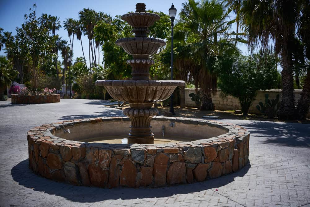 A stone fountain in Todos Santos Mexico in a small plaza with palm trees in the background.
