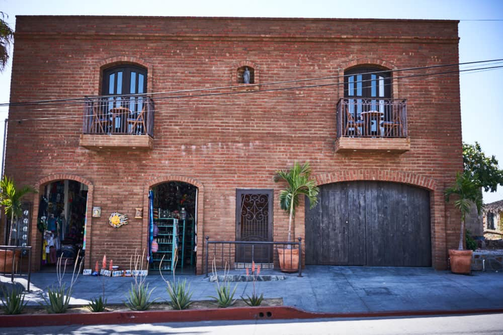 A two-story brick building with a storefront and a wooden garage door in Todos Santos, Mexico.