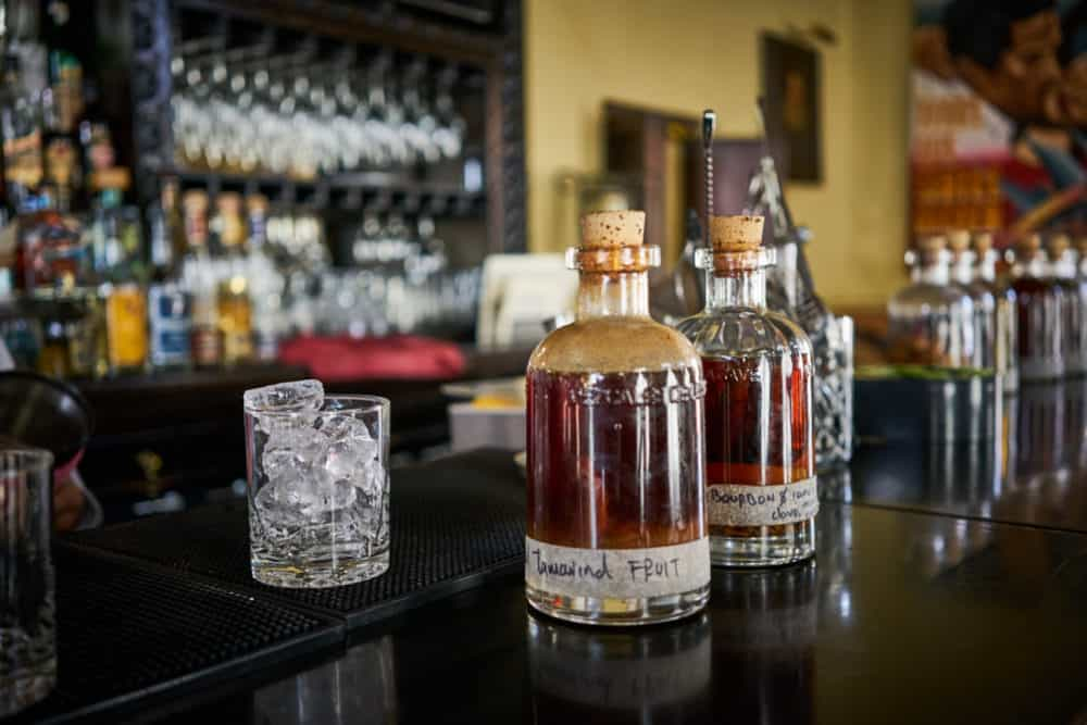 Two glass bottles of infused syrups for cocktails at the Todos Santos Inn, sitting on a wooden bar with liquor bottles in the background.