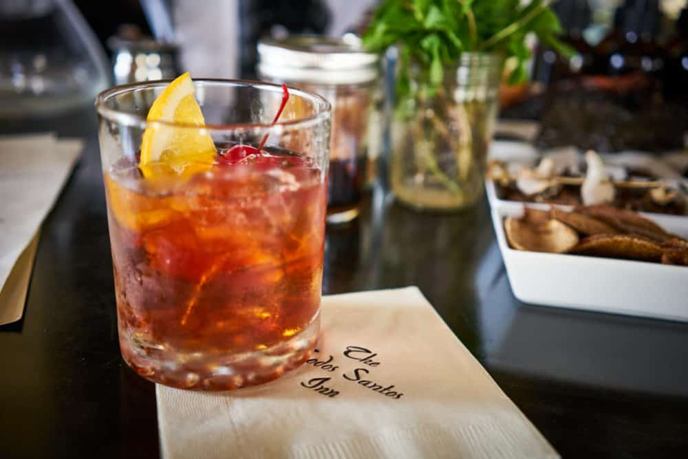 "An Old Fashioned cocktail sits on a bar on a napkin that reads, ""The Todos Santos Inn"". Other garnishes for drinks are in the background. Photo by Brian Cummings."