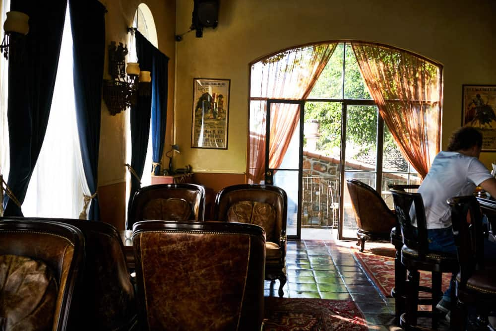 The bar at the Todos Santos Inn. A high-ceilinged room with yellow walls, stone tile floors, big leather arm chairs and large arched windows with blue curtains. the far wall has large glass doors that open onto a courtyard.