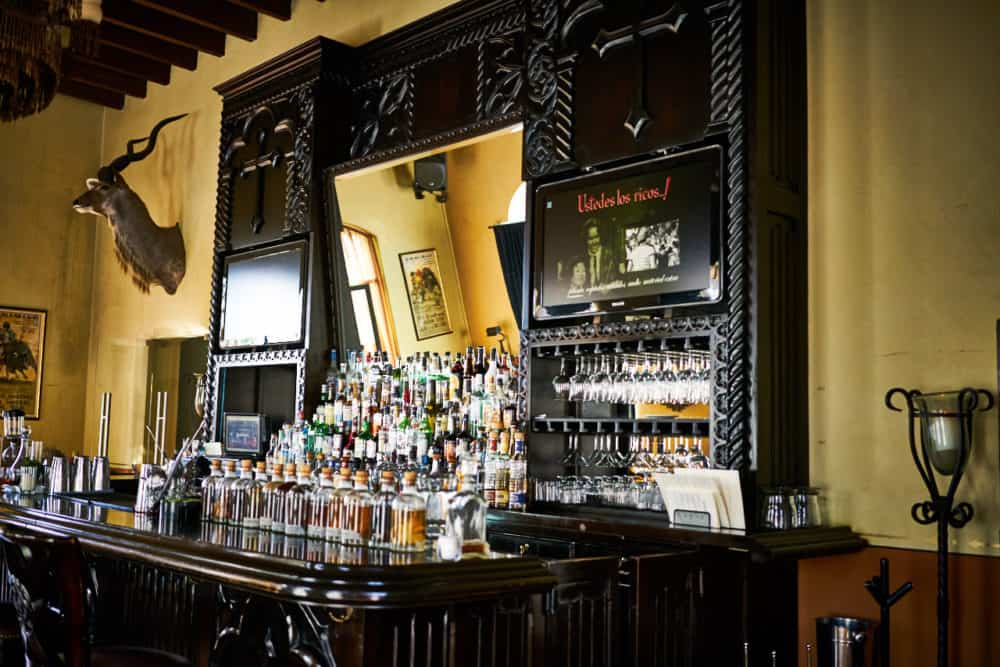 The bar at the Todos Santos Inn features a large wooden bar with mirrors and elaborate woodwork. The room has yellow walls and a deer head, and beams on the ceiling.