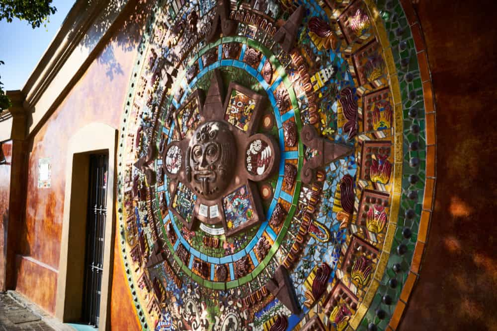 A colorful Aztec calendar in relief on the side of a building in Todos Santos, Mexico, by artist Donna Billick.