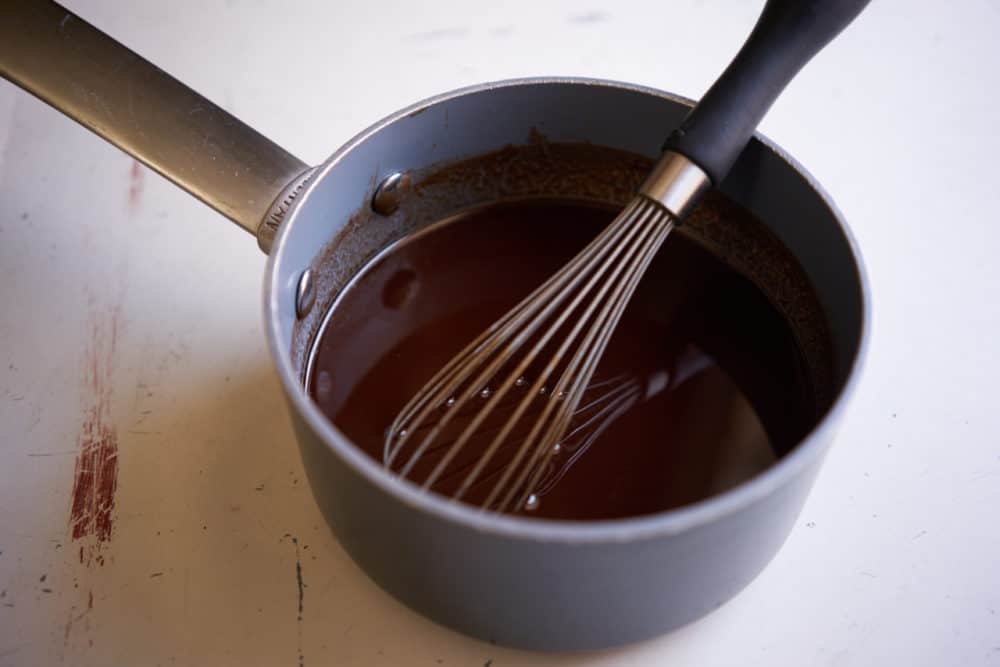 A small sauce pan with a whisk containing melted chocolate.