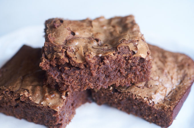 Three square-shaped brownies displayed on a white plate.