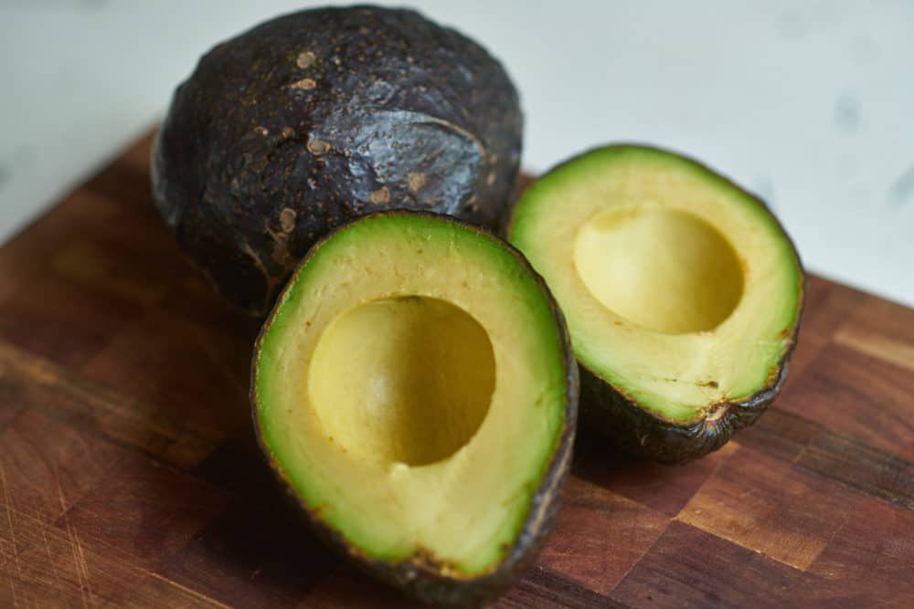 A halved avocado and a whole avocado arranged on a wooden cutting board.