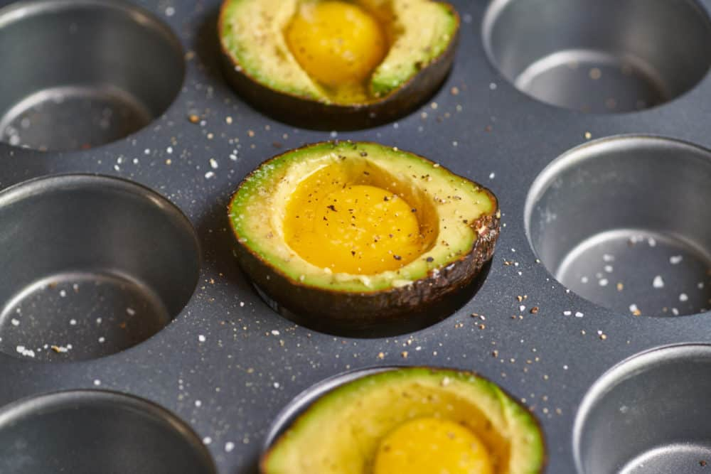 Raw eggs inside avocado halves sitting inside the wells of a muffin pan.
