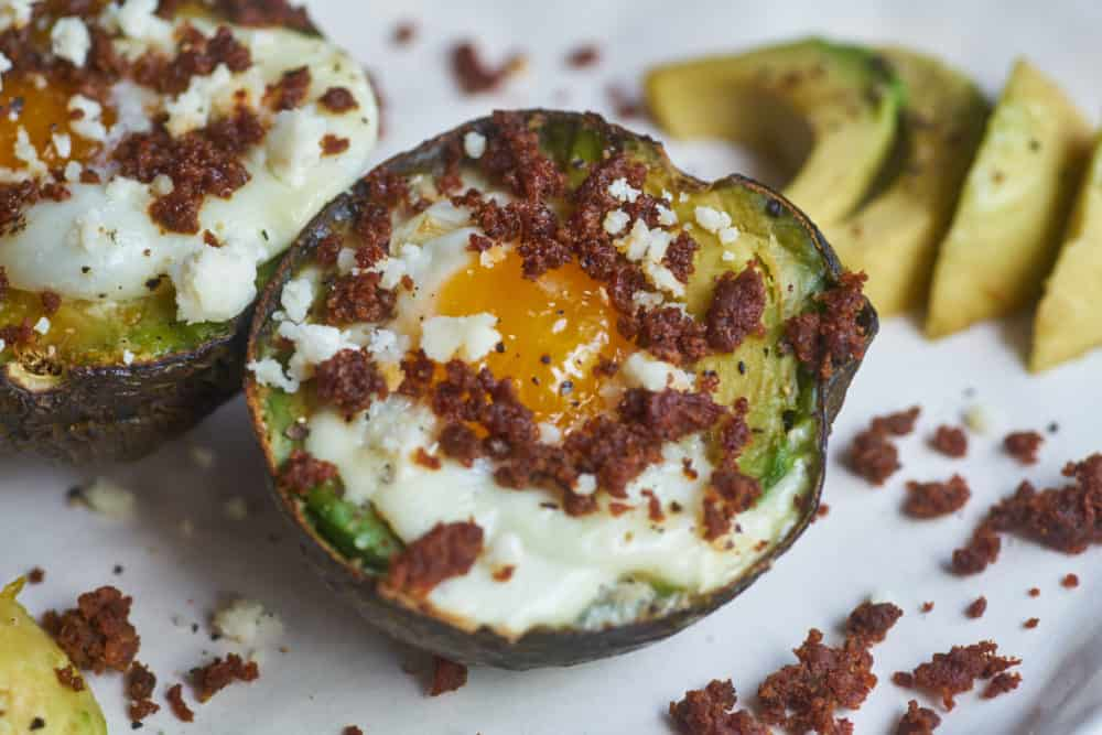 Baked eggs in avocados with chorizo and avocado slices.