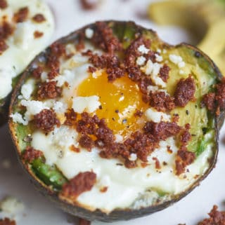 Egg baked in an avocados half topped with chorizo and queso fresco displayed on a white plate, surrounded by bits of chorizo and avocado slices.