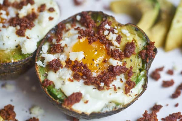Egg baked in an avocado half topped with chorizo and queso fresco displayed on a white plate, surrounded by bits of chorizo and avocado slices.