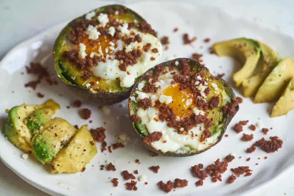 Two eggs baked in an avocado half topped with chorizo and queso fresco displayed on a white plate, surrounded by bits of chorizo and avocado slices.