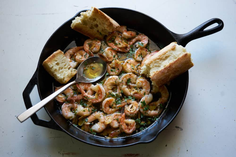 A cast iron skillet filled with garlic shrimp (gambas al ajillo). A silver spoon and torn french bread are also in the pan.