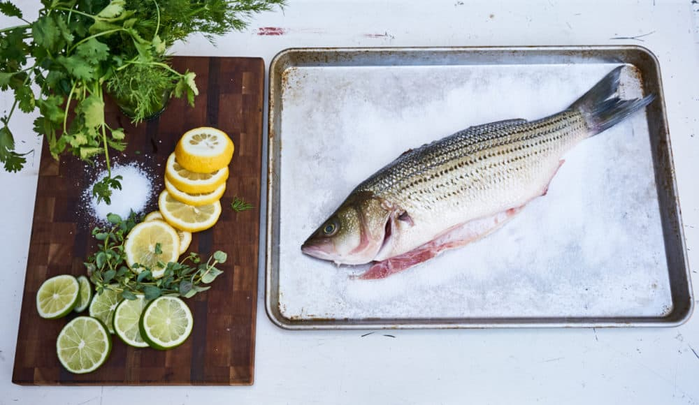 Whole fish on a bed of salt on a sheet pan next to a cutting board with fresh herbs and sliced lemons and limes.