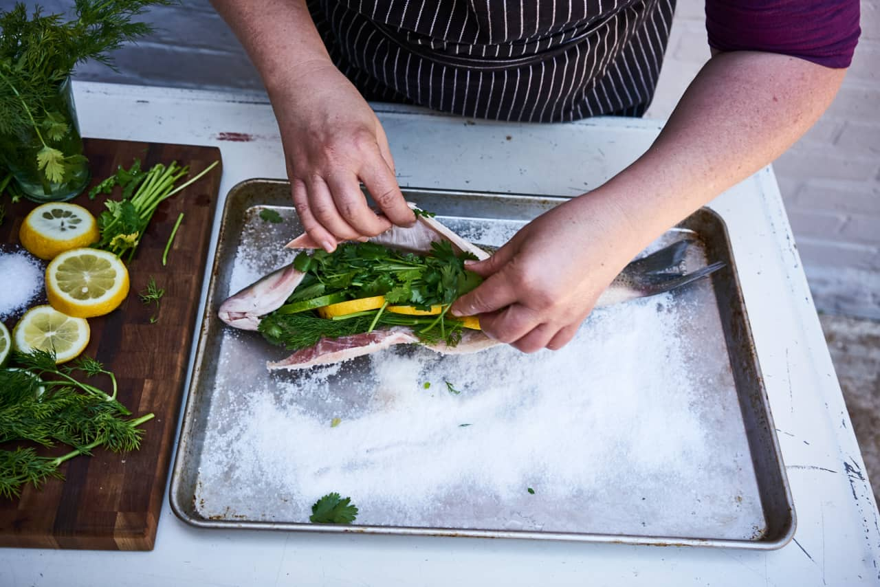 A woman's hands are shown preparing a salt baked whole fish, she stuffs a whole fish with lemon, lime and fresh herbs. The fish is laying on a bed of salt on a sheet pan.
