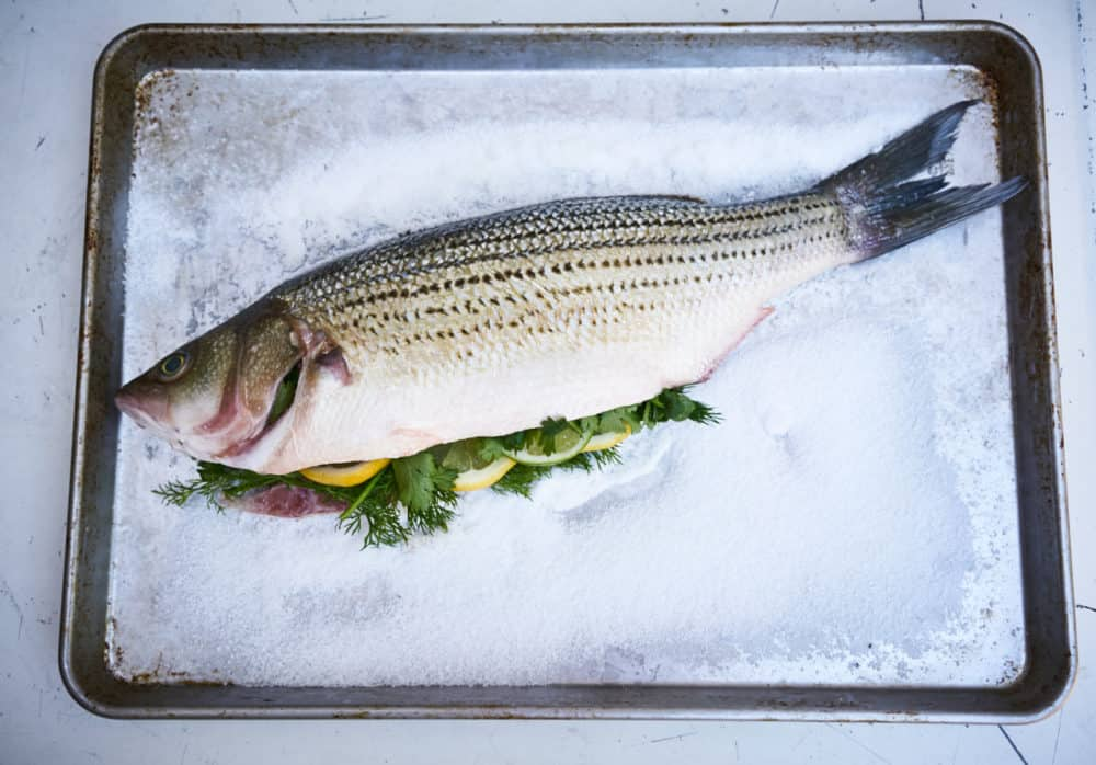 A whole striped bass stuffed with herbs and citrus fruit sits on a bed of salt on a silver sheet pan.