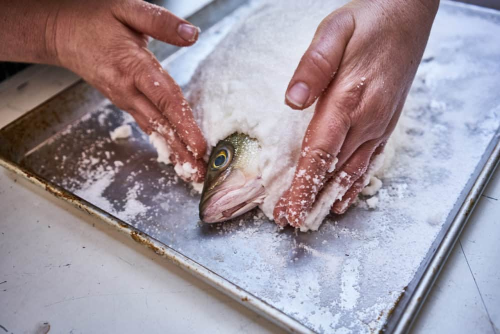 A woman's hands are shown spreading a kosher salt and egg white mixture onto a whole fish. The fish's head is exposed.