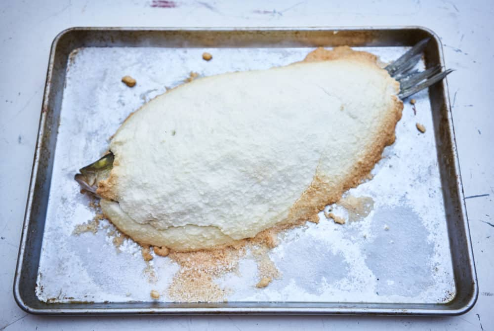 A whole fish that has been baked in a salt crust is shown on a silver sheet pan. The edges of the salt are browned.