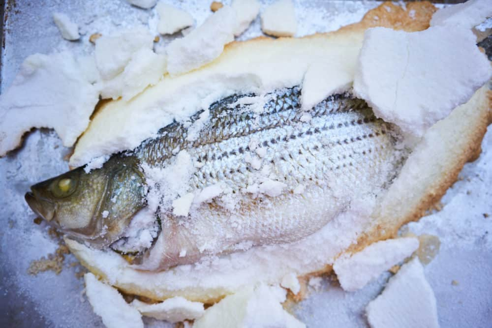 Whole fish baked in salt on a silver tray surrounded by chunks of salt crust.