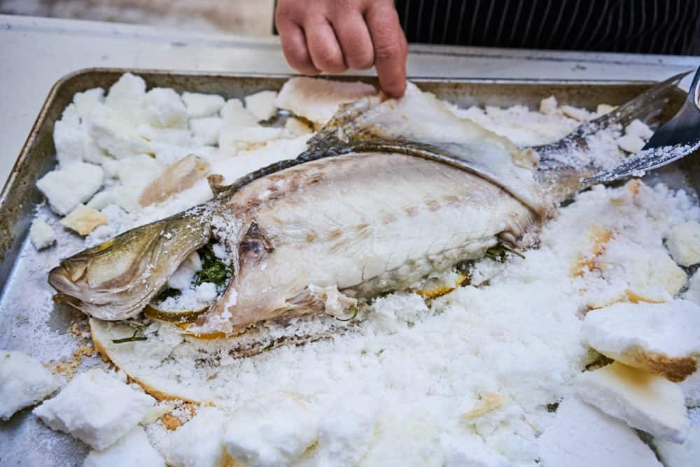 A woman's hands are shown peeling back the skin of a whole fish that has been baked in salt.