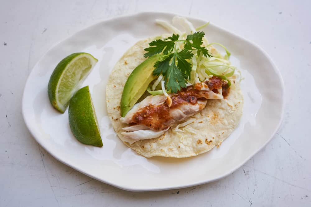 A fish taco dressed with salsa, cilantro, cabbage and avocado, with two lime wedges on the side.