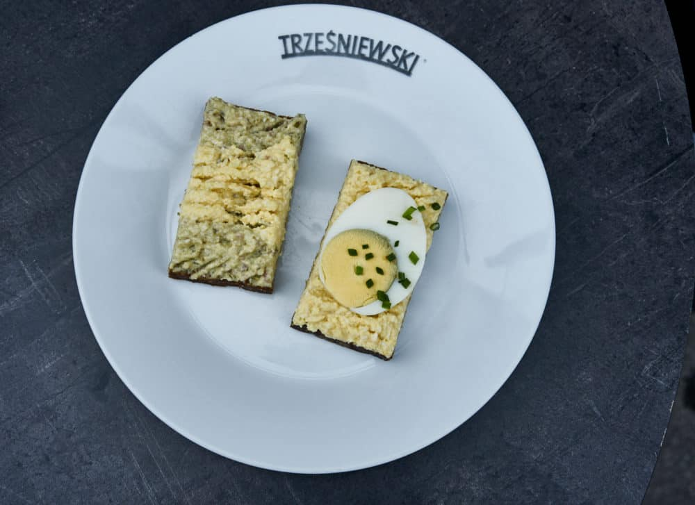 A white plate with two Trzesniewski open-faced sandwiches with hard boiled egg and egg salad.