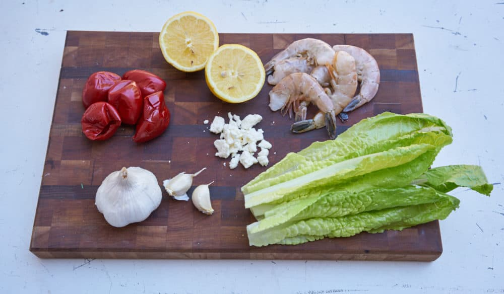 Romaine lettuce leaves, feta cheese, garlic, cherry peppers, lemon and raw shrimp displayed on a wooden cutting board.