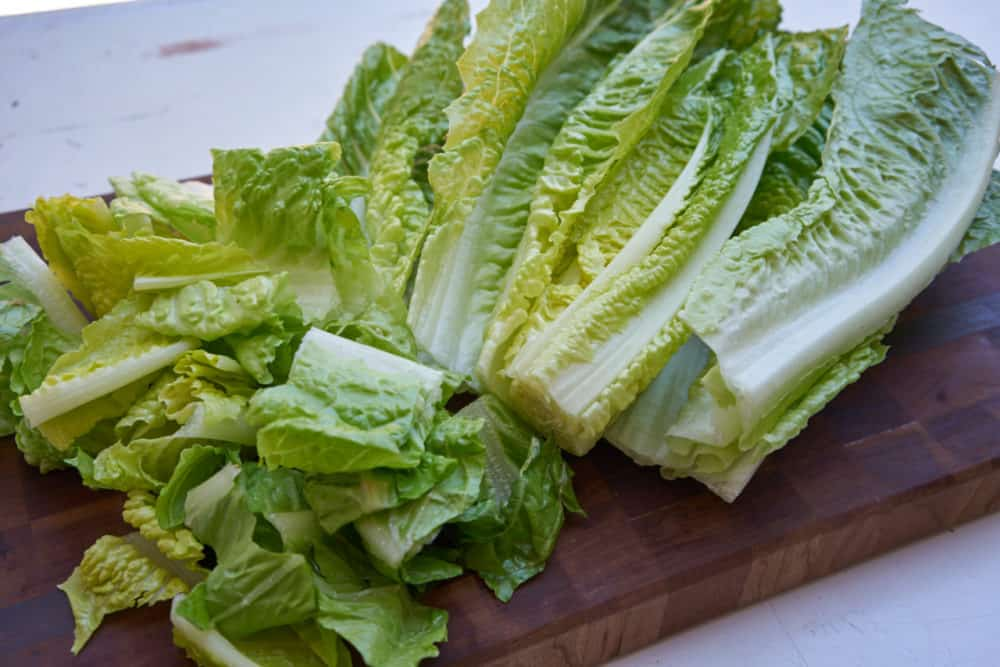 Chopped romaine lettuce on a wooden cutting board.