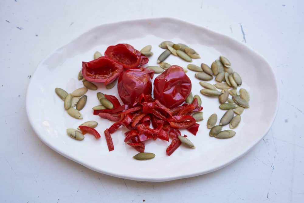 Pepitas (pumpkin seeds) and cherry peppers on a white plate.