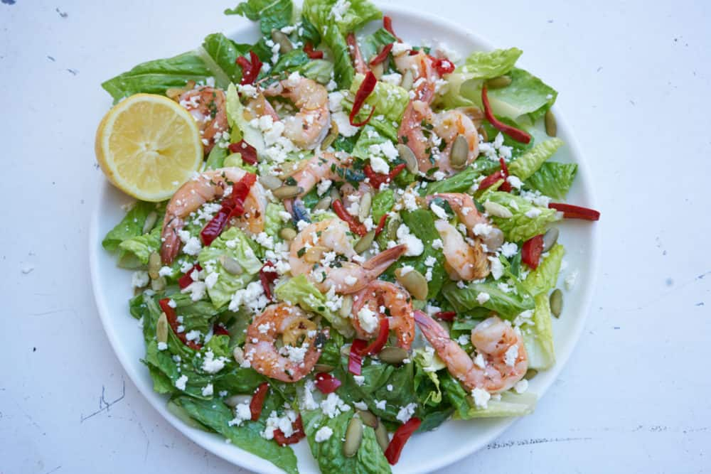 Large round plate of green salad with shrimp, romaine lettuce, cherry peppers, pepitas and feta cheese, garnished with a half a lemon.