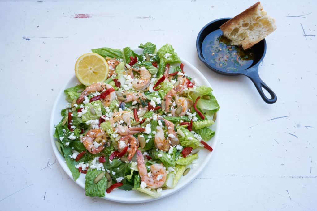 Large round plate of green salad with shrimp, romaine lettuce, cherry peppers, pepitas and feta cheese, garnished with a half a lemon. A small cast iron pan filled with garlic oil and a hunk of bread sits to the right of the plate.