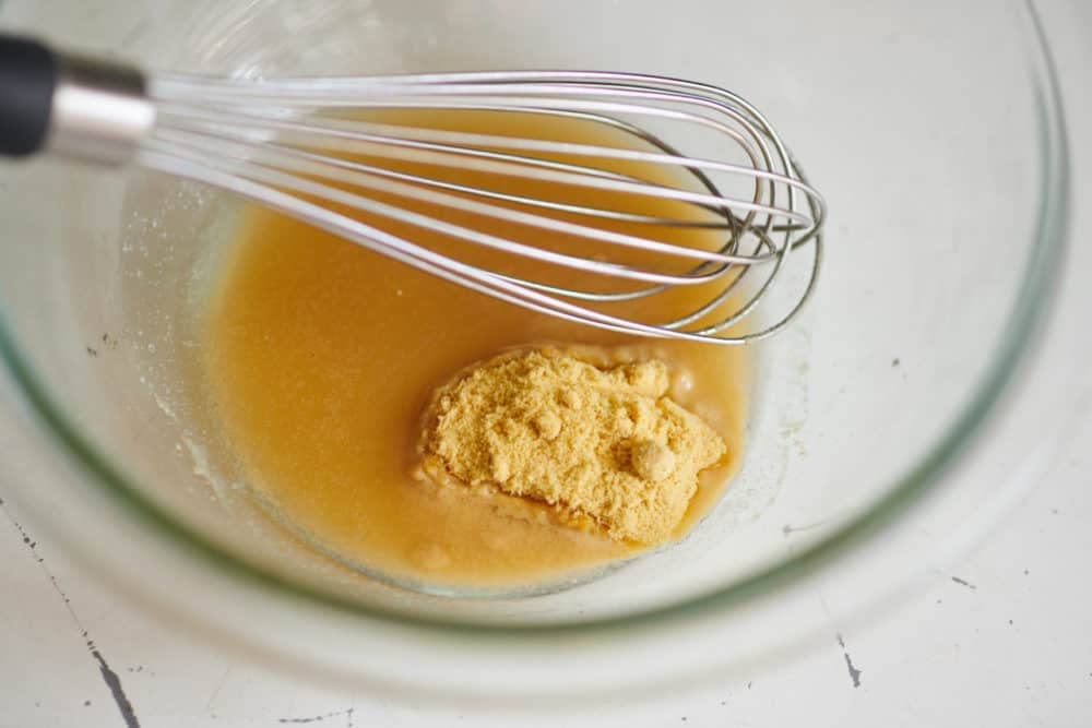 A glass bowl containing a whisk, apple cider vinegar and mustard powder.