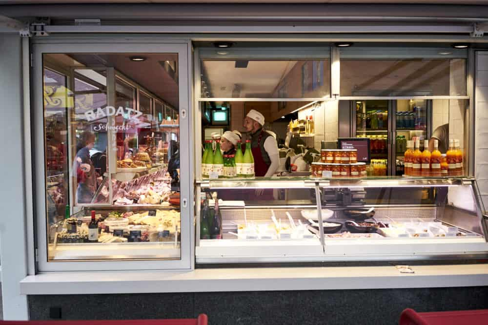 Radatz butcher shop at Rochusmarkt in Vienna. Looking through a window toward a man in a white hat working at a meat counter. Cheeses and cold salads are displayed in the window.