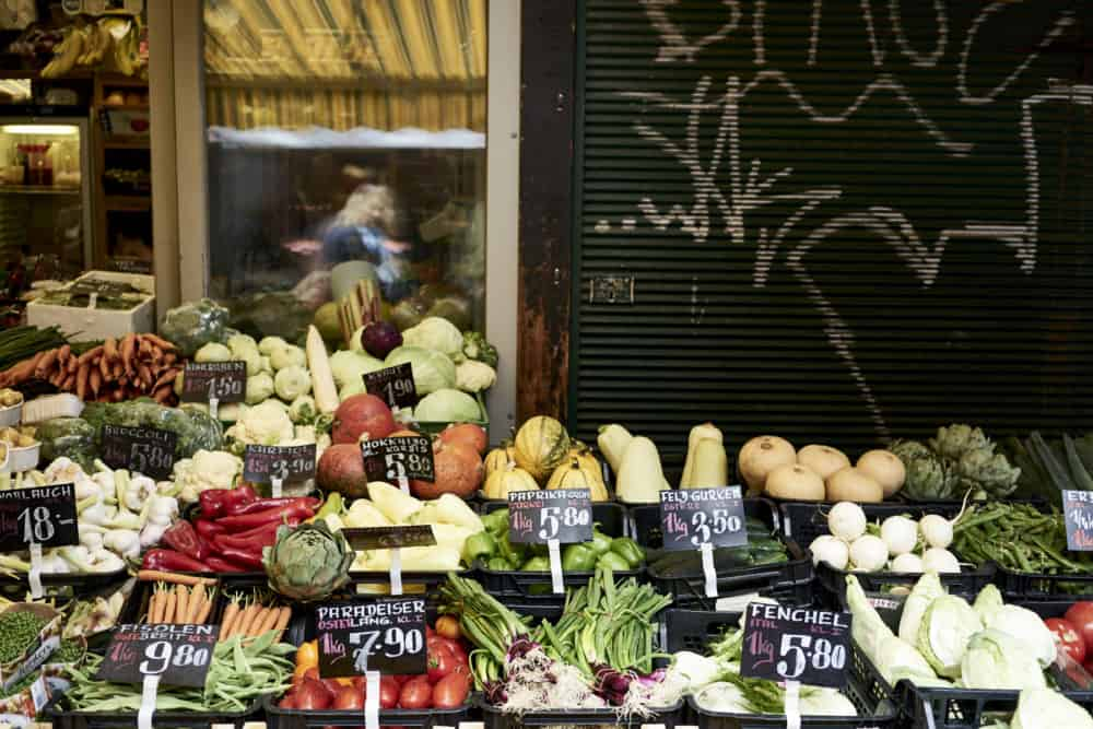 Produce on display at Rochusmarkt, Vienna, including squash, green onions, and tomatoes.
