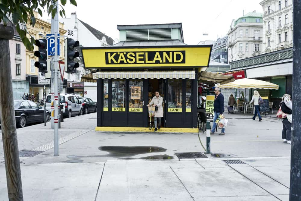 Käseland shop at Rochusmarkt Vienna. A yellow and black building, a woman is exiting the front door with a scooter.
