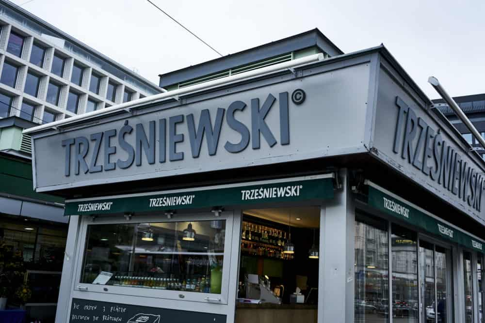 Trzesniewski location at Rochusmarkt Vienna. A small grey building with clear glass walls and green awnings.