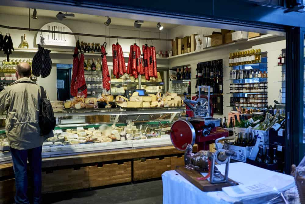 A cheese and charcuterie stand at Naschmarkt in Vienna. A deli case holds a variety of cheeses and cured salamis hang from the ceiling. A meat grinder is in the foreground.